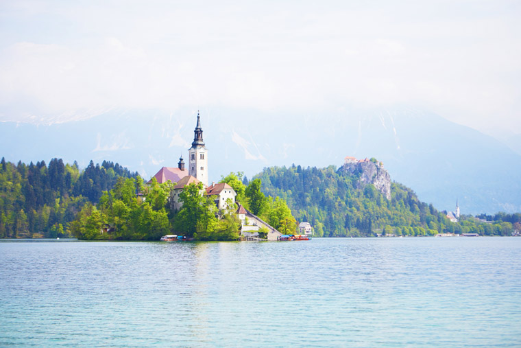 castle on mountain and cathedral in center of bled lake slovenia
