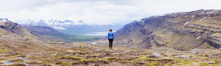 standing on the edge overlooking fjord glacier in iceland