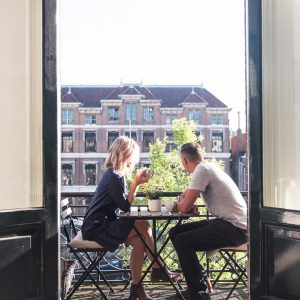 Couple on balcony in Amsterdam canal house Airbnb