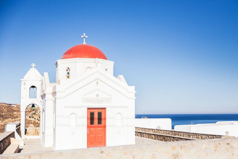 church with red roof near beach mykonos island