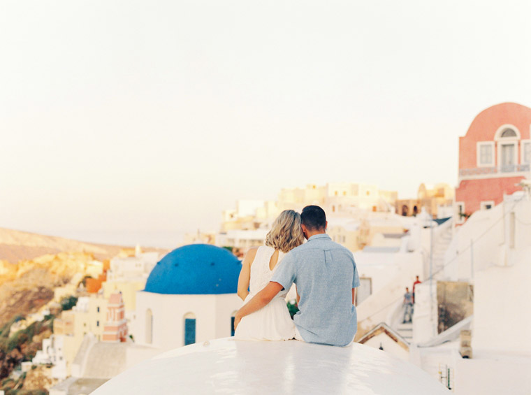 Couple overlooking Santorini Rooftops Enagement Session Oia Town