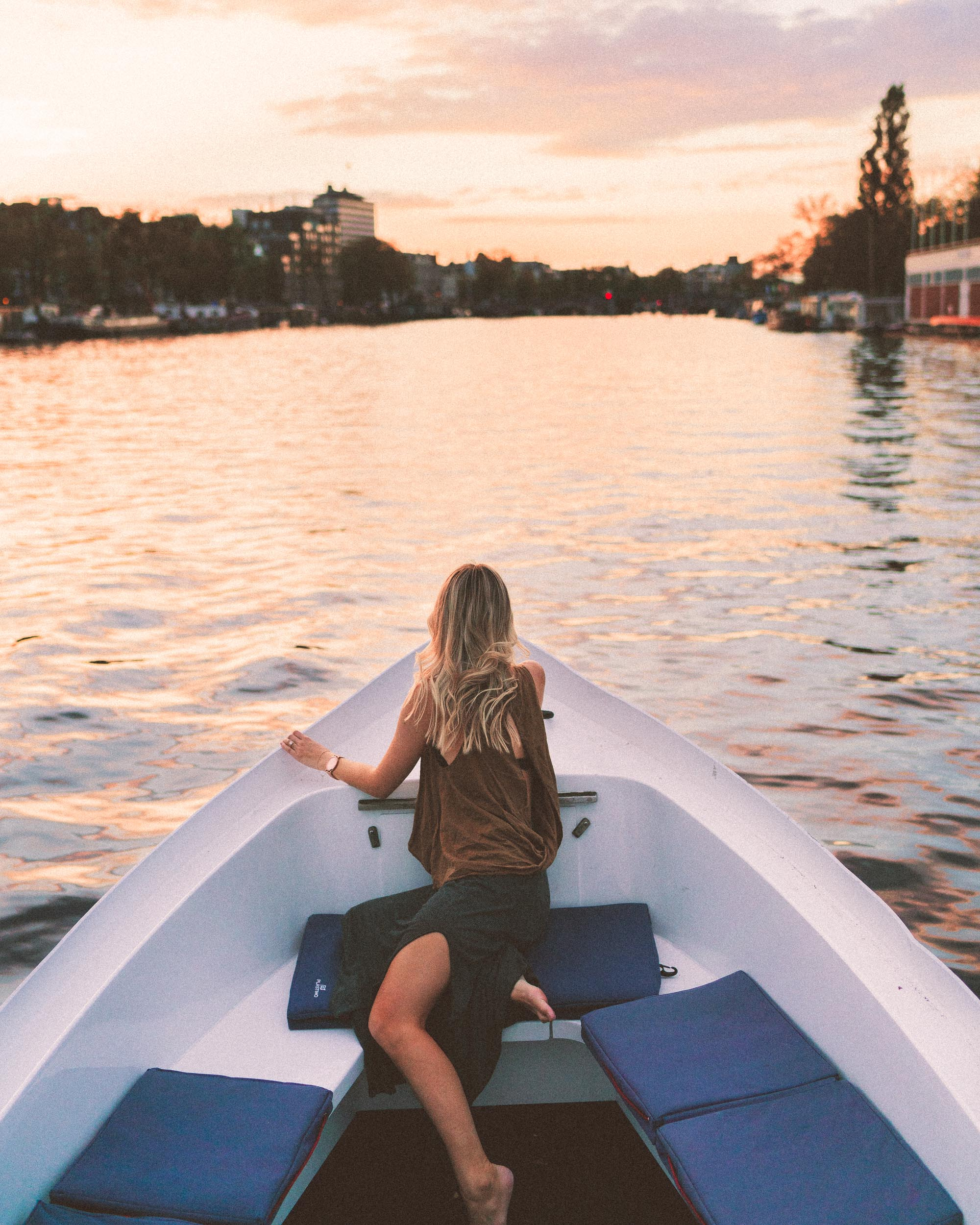 Boating down Amstel at sunset in summer, Amsterdam, The Netherlands