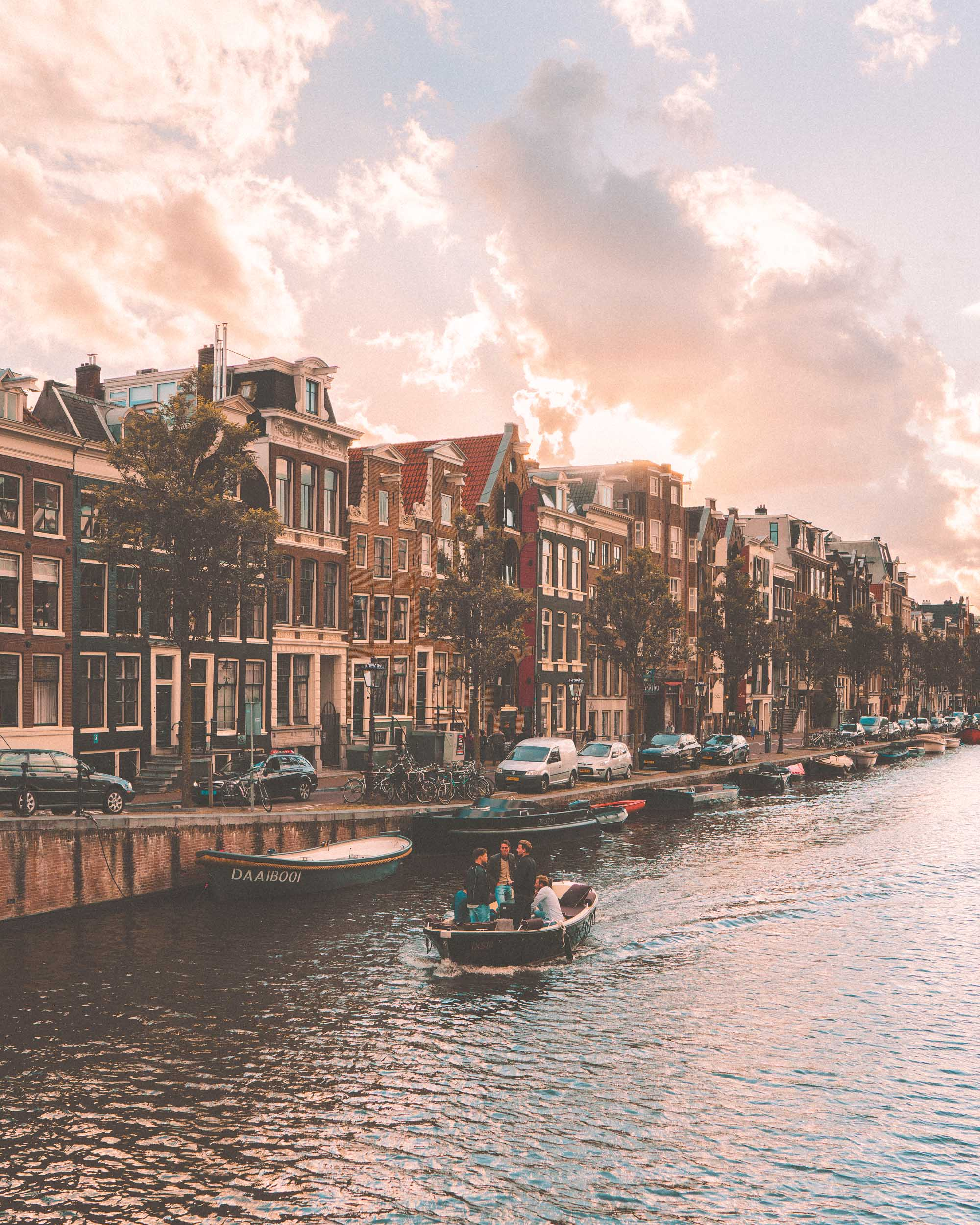 Sunset in Amsterdam over prinsengracht canal with boats in summer, The Netherlands