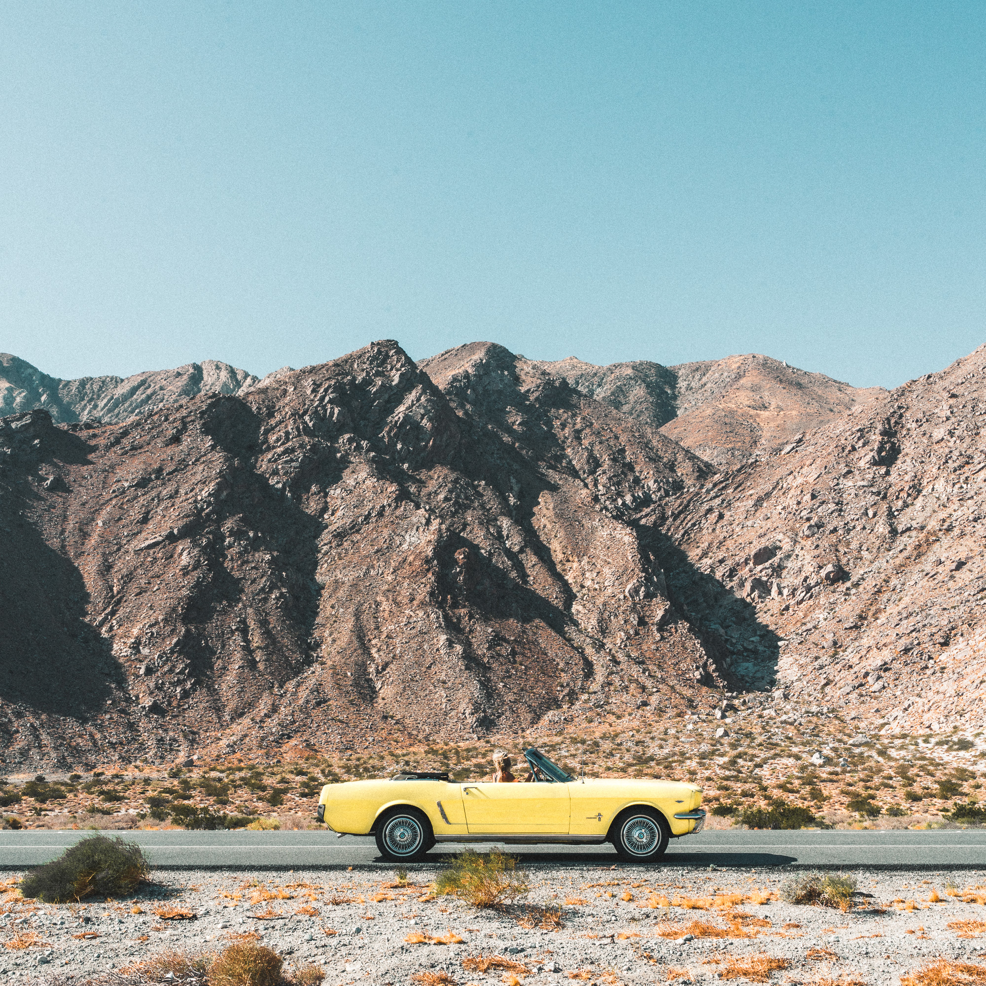 vintage yellow mustang road trip in the desert to palm springs