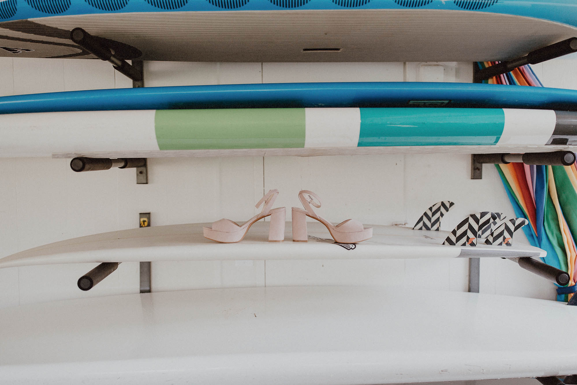 Blush wedding shoes on surfboard