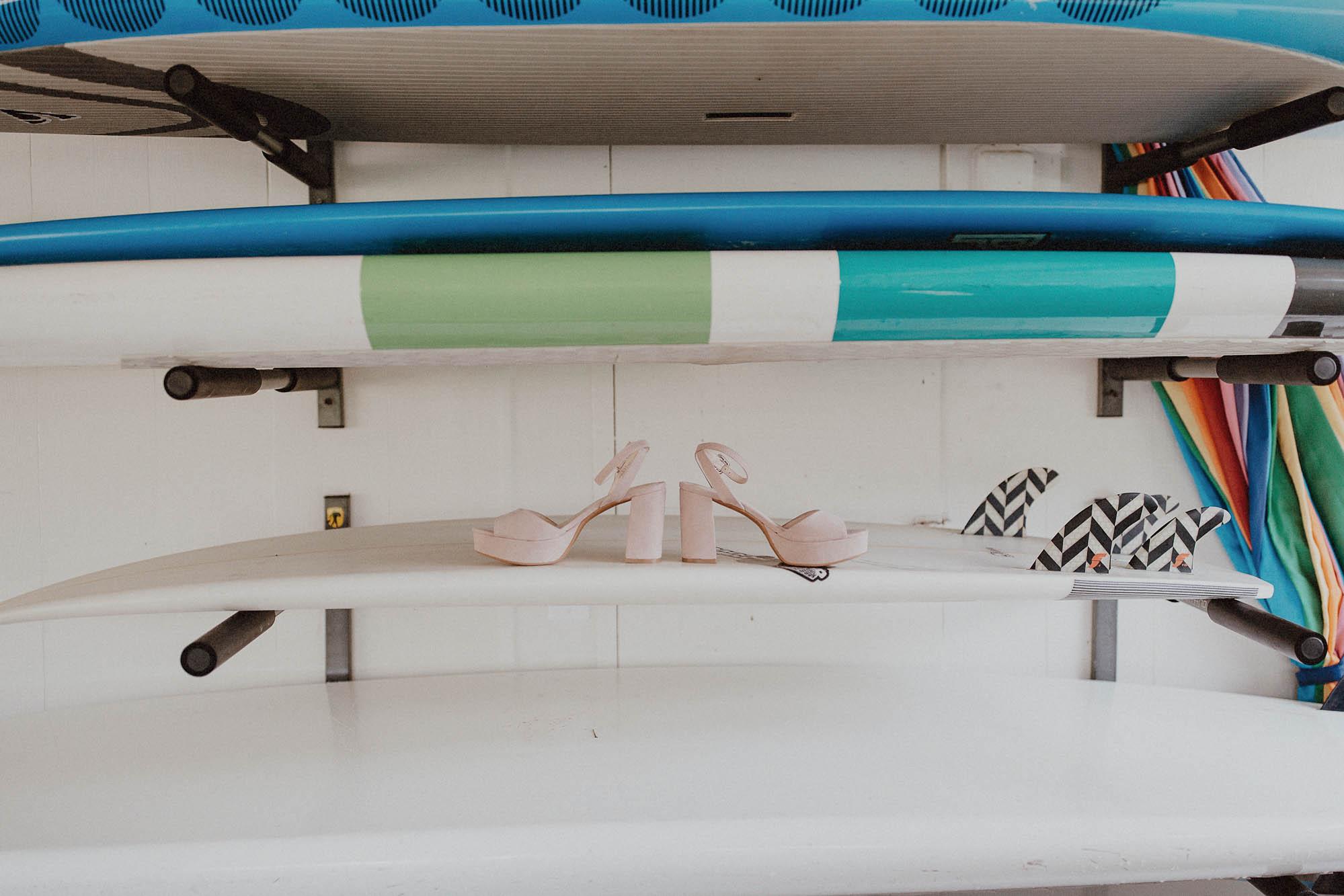 Blush wedding shoes on surfboard