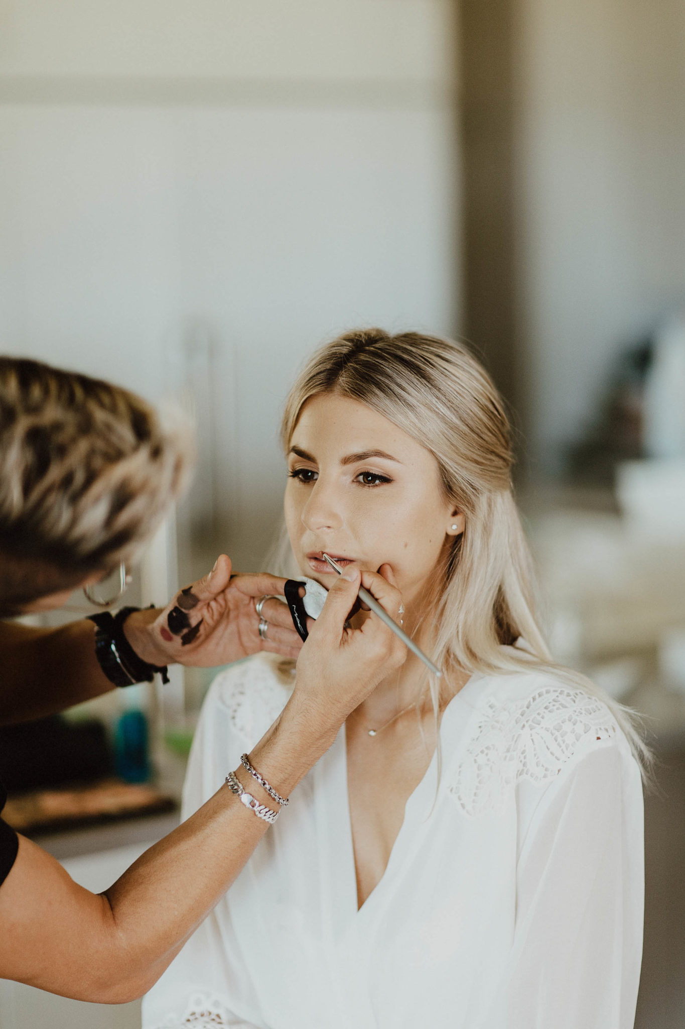 Bride getting ready white lace robe in chair wedding day