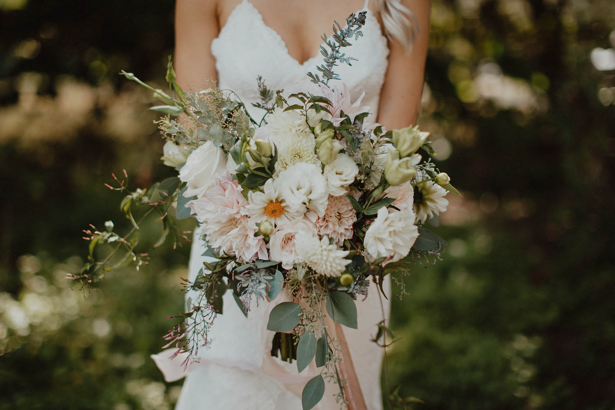 Blush and white floral bouquet with dahlias tuberose garden roses and greenery pink ribbon