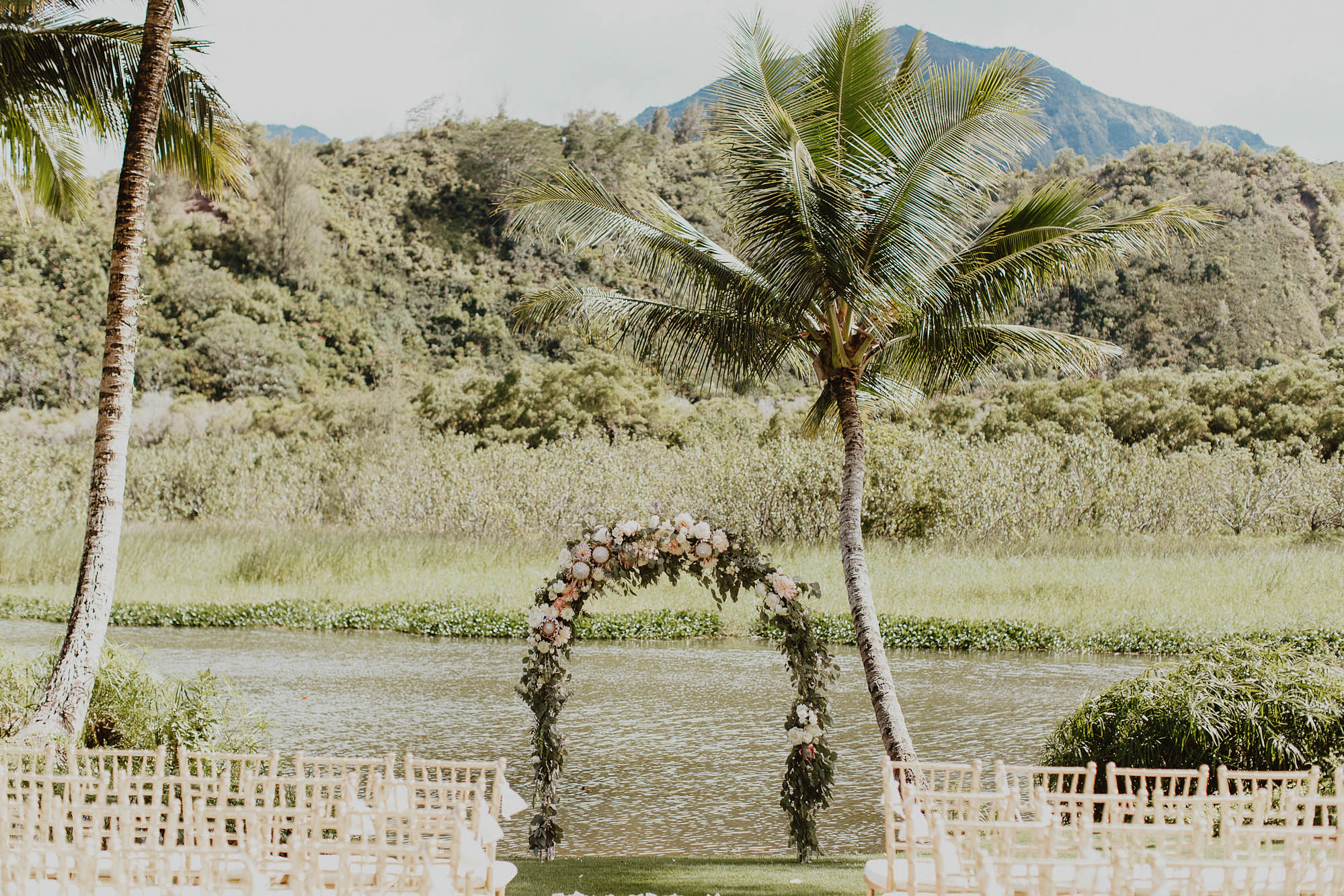 Floral arch palm trees gold chivari chairs aisle set up