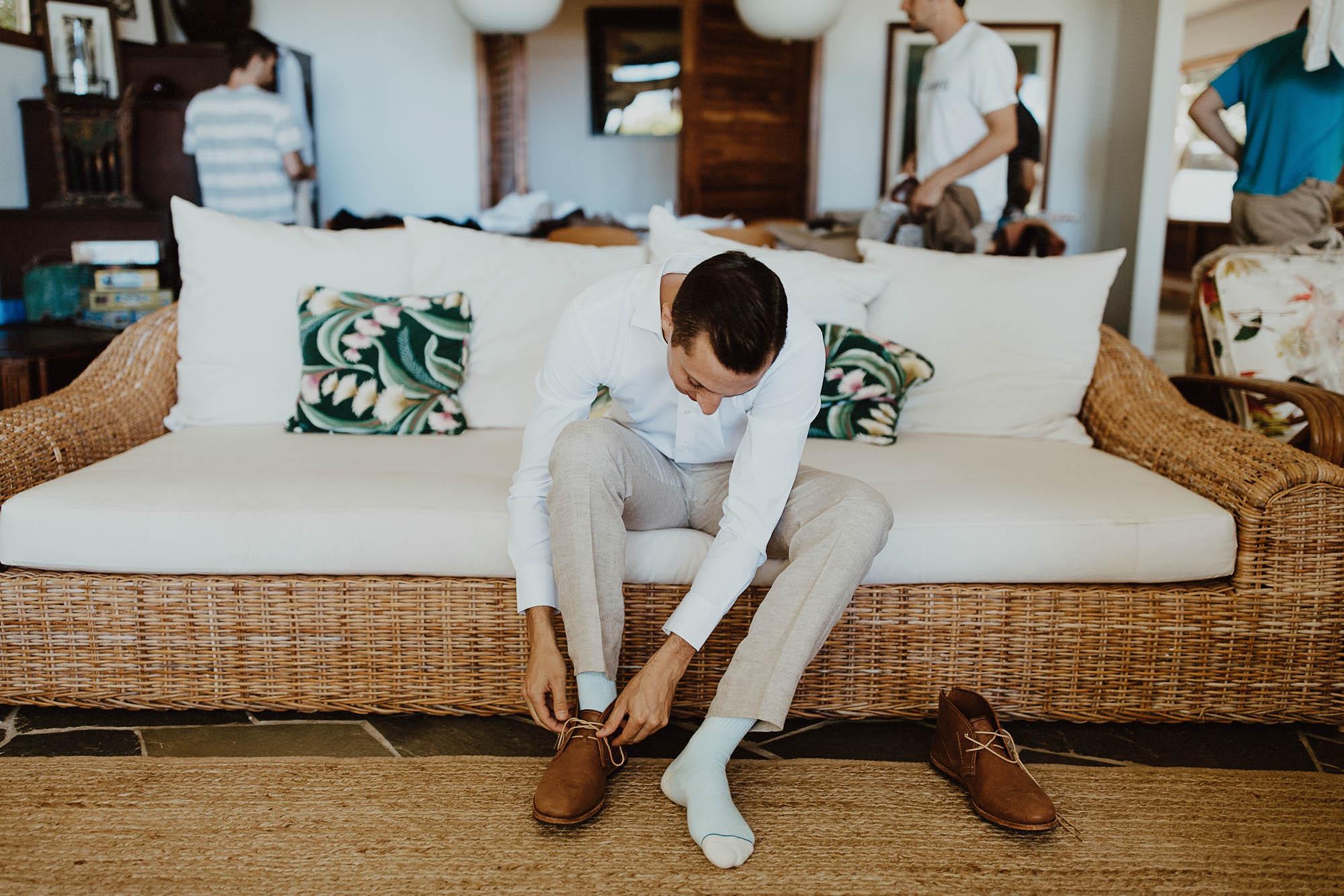 Groom putting on his shoes kauai hawaii north shore