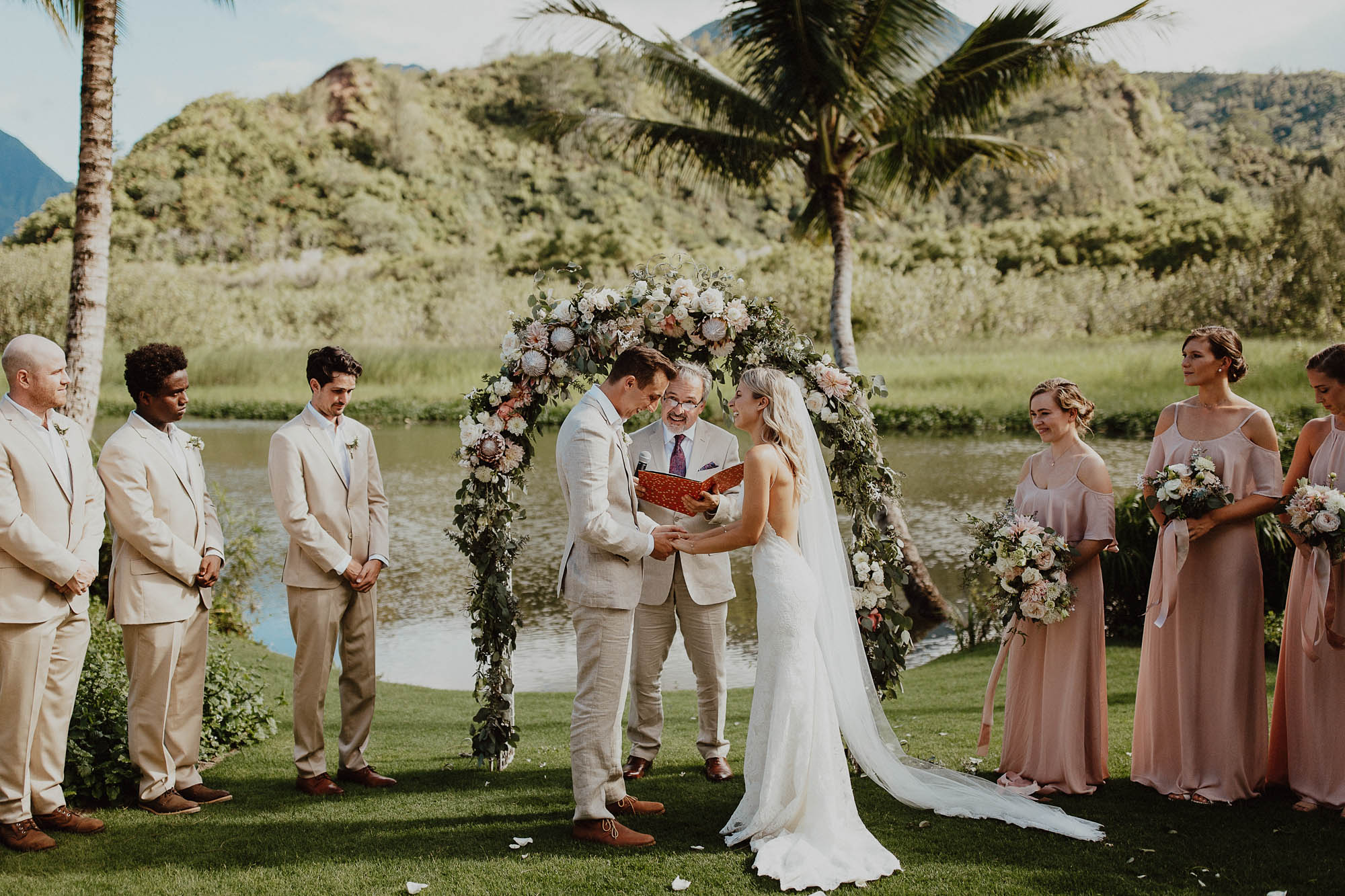 Saying vows under arch north shore kauai wedding day