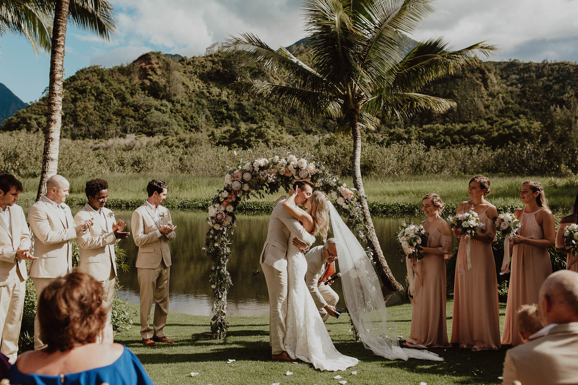Kissing under arch after saying i do north shore kauai wedding day