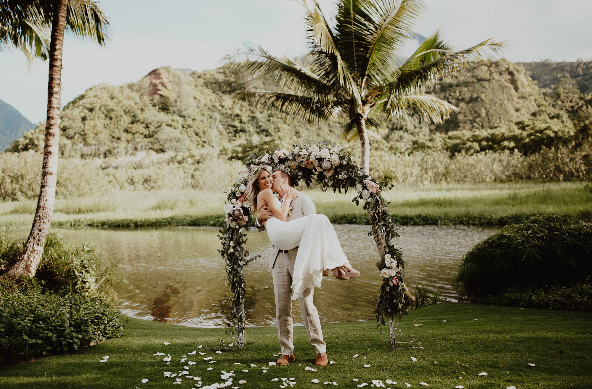 Firemans carry under blush green white arch on our wedding day north shore kauai hawaii