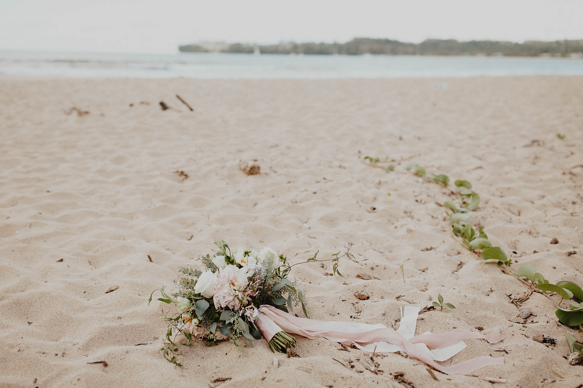 Blush white floral bouquet dahlias tuberose greenery on the beach hawaii