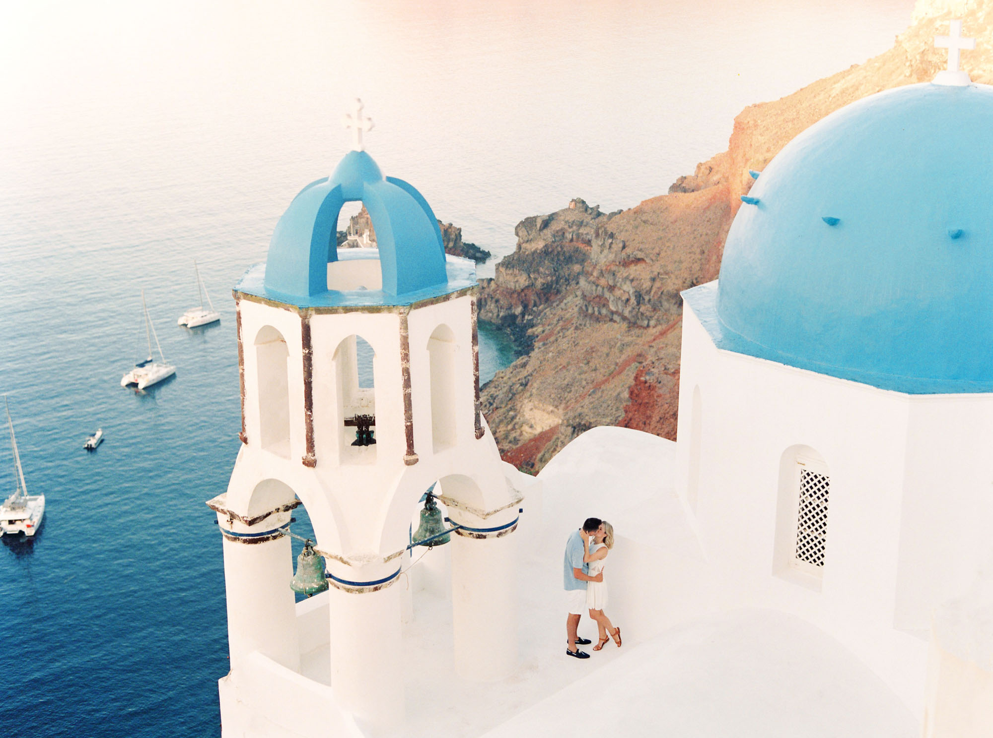 Kissing on the rooftops of Oia in Santorini, Greece