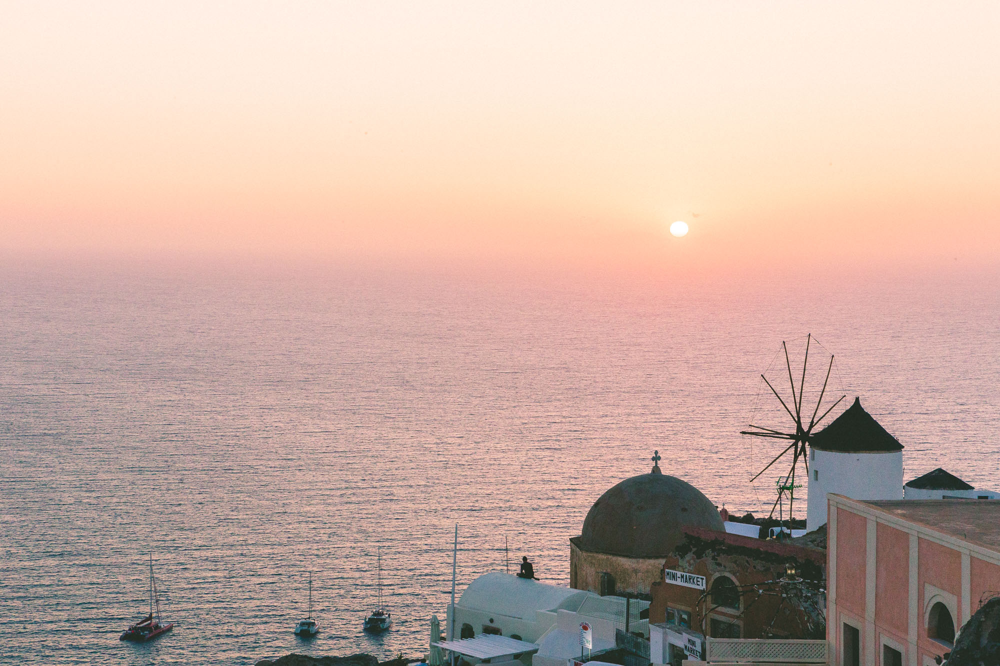 Sunset over Greek windmills in Santorini, Greece
