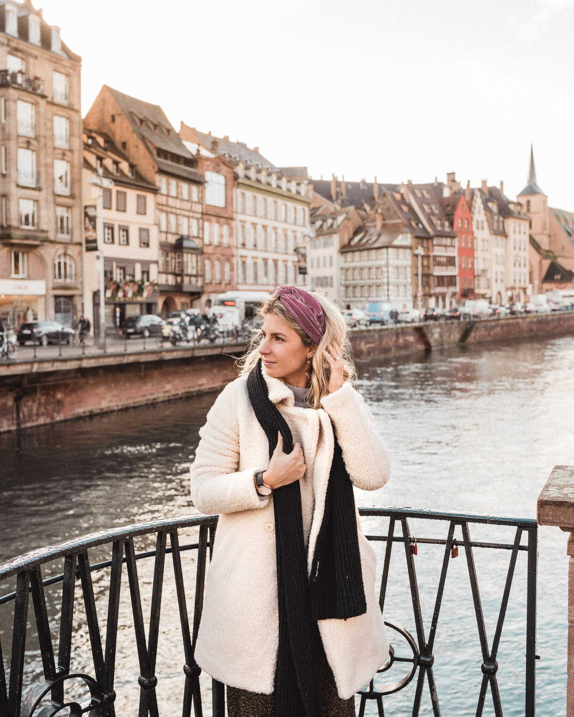Travel blogger Selena Taylor with pastel houses on the river in strasbourg france