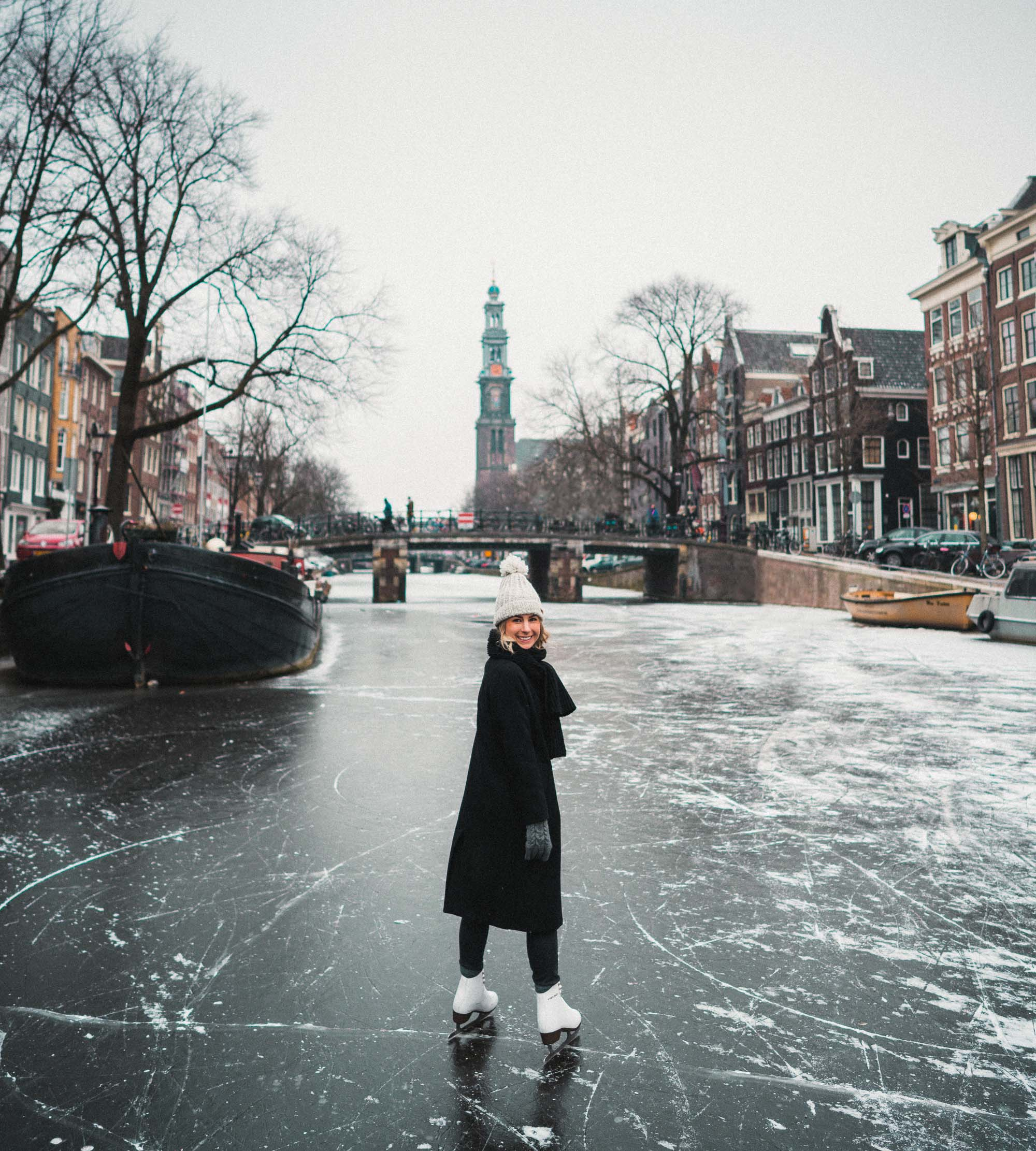 Travel blogger Selena Taylor ice skating on the frozen canals in Amsterdam The Netherlands