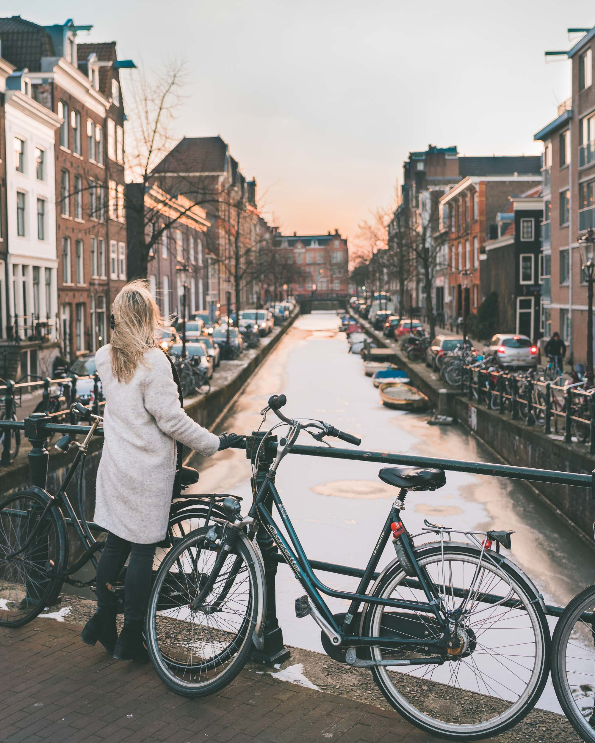 Travel blogger Selena Taylor in front of the frozen canals in Amsterdam The Netherlands