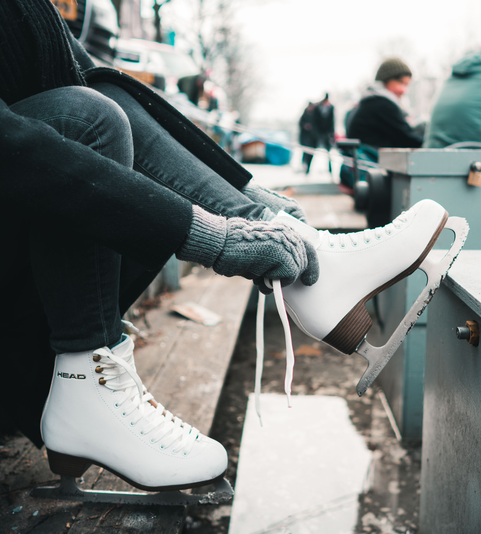 Travel blogger Selena Taylor putting on ice skates for the frozen canals in Amsterdam The Netherlands