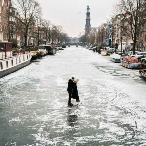 Travel bloggers Selena Taylor and Jacob Taylor ice skating on the frozen canals in Amsterdam The Netherlands