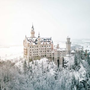Neuschwanstein Castle in the snow in winter from mary's bridge Marienbrucke lookout best spot to photograph german fairytale castle