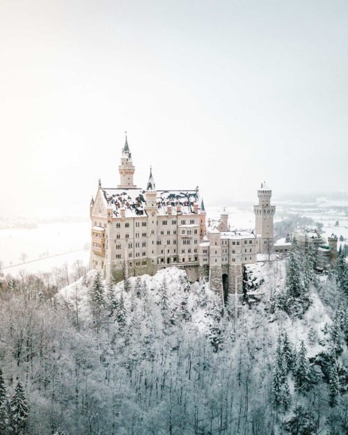 Neuschwanstein Castle in the snow in winter from mary's bridge Marienbrucke lookout best spot to photograph german fairytale castle