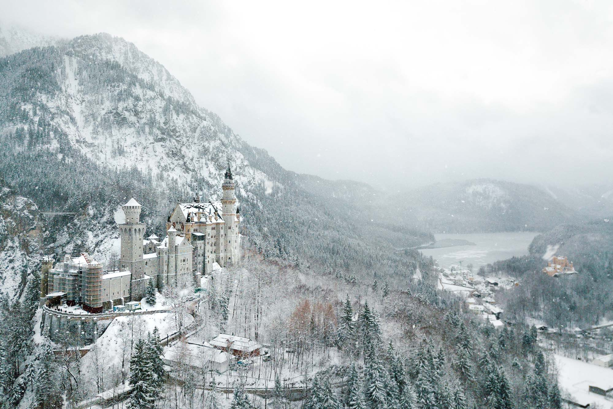 Neuschwanstein Castle in the snow in winter with lake behind best spots to photograph german fairytale castle