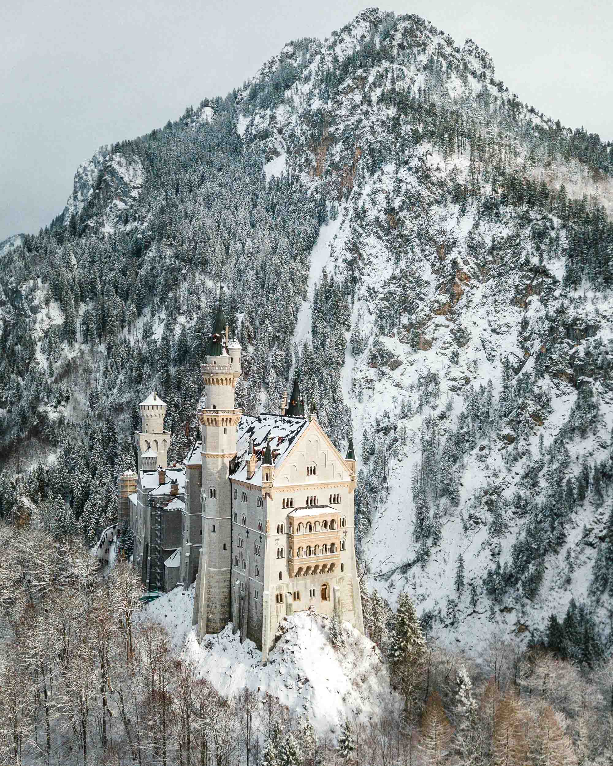 Neuschwanstein Castle in the snow in winter with mountains behind best spots to photograph german fairytale castle