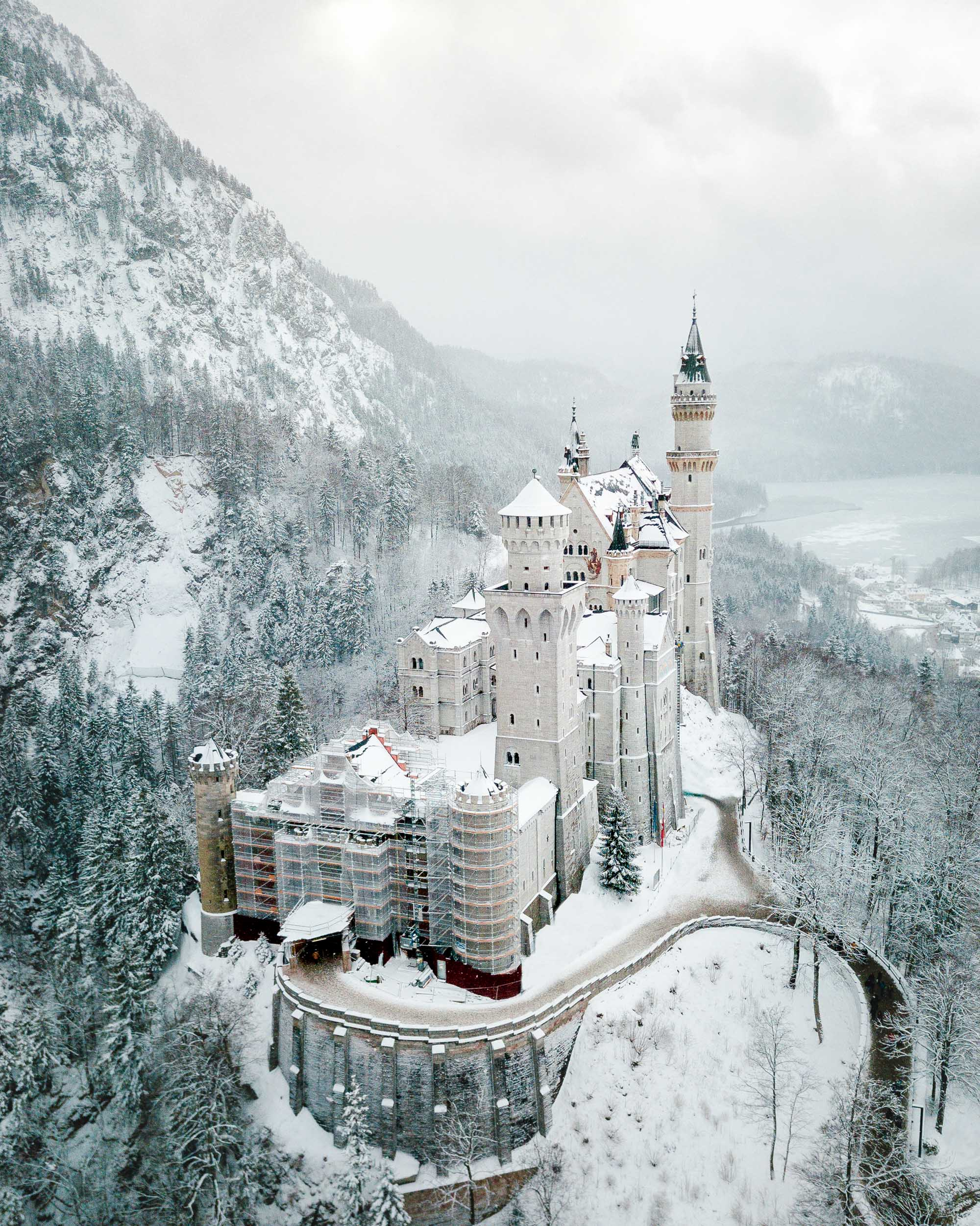 Neuschwanstein Castle in the snow in winter birds eye view Marienbrucke lookout best spot to photograph german fairytale castle