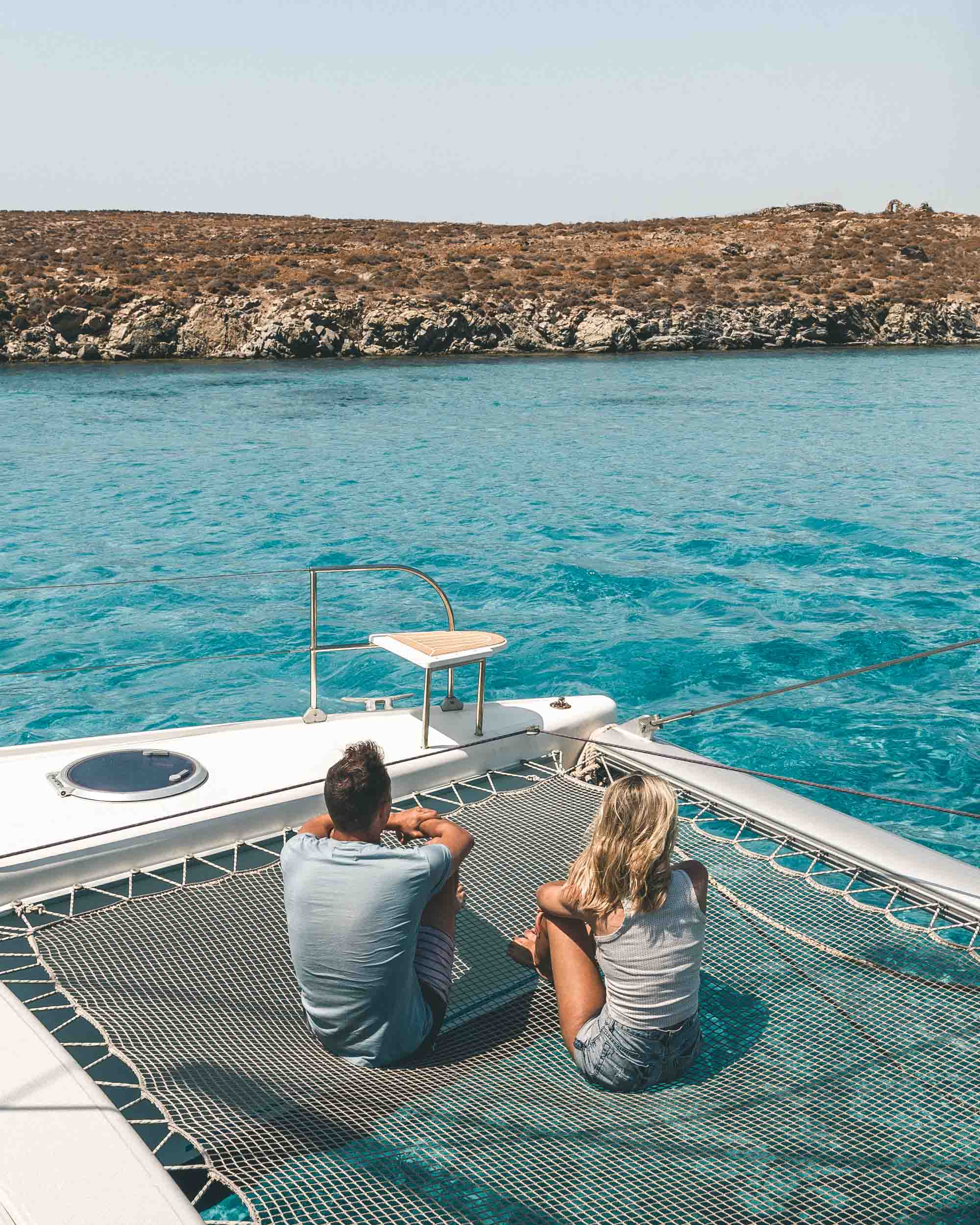 Sailing on the coast of mykonos in the greek islands selena and jacob taylor of finduslost travel bloggers