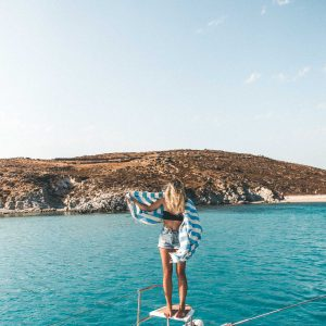 Sailing on the coast of mykonos in the greek islands mediterranean sea selena taylor of finduslost travel blogger