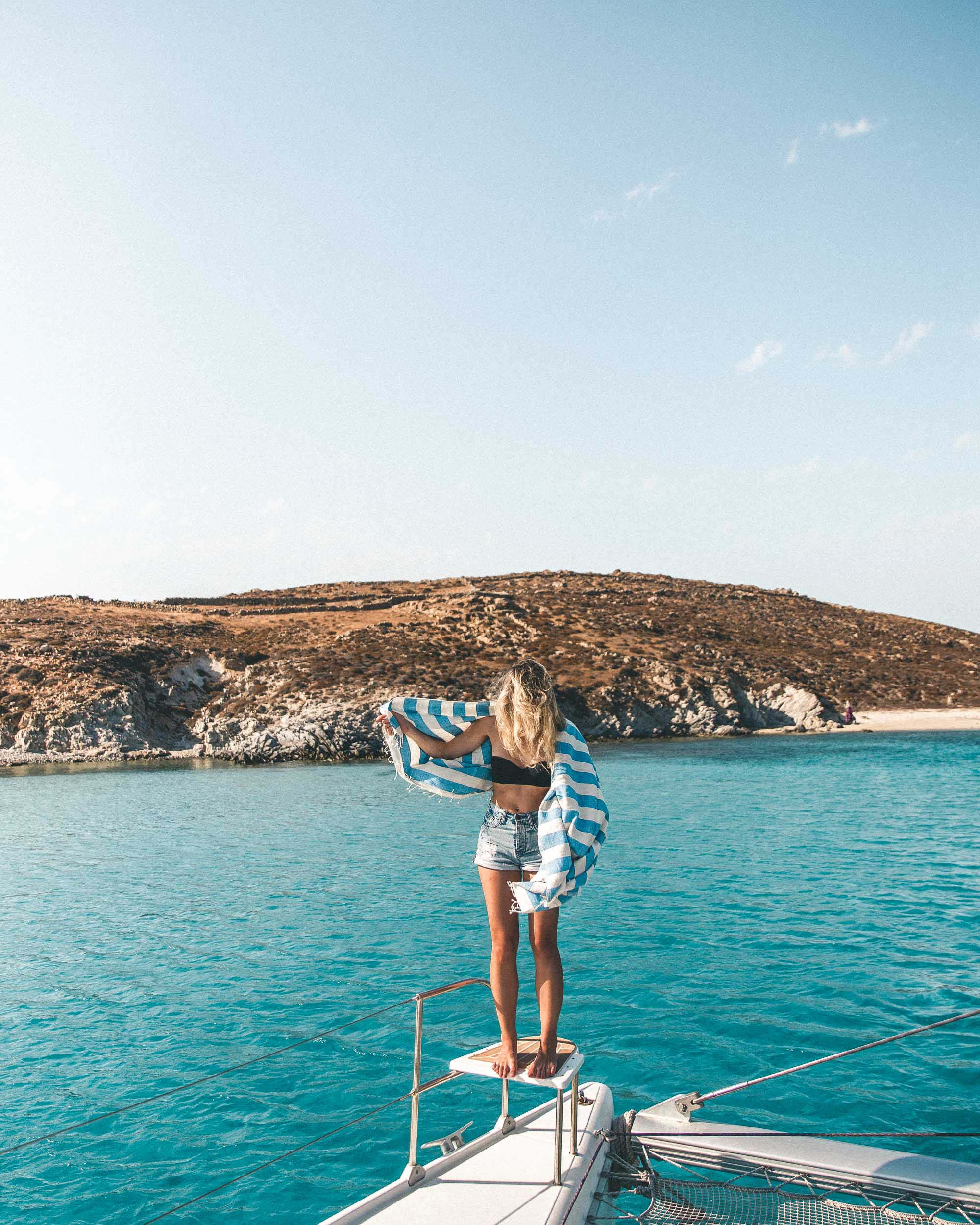 Sailing on the coast of mykonos in the greek islands mediterranean sea selena taylor of finduslost travel blogger