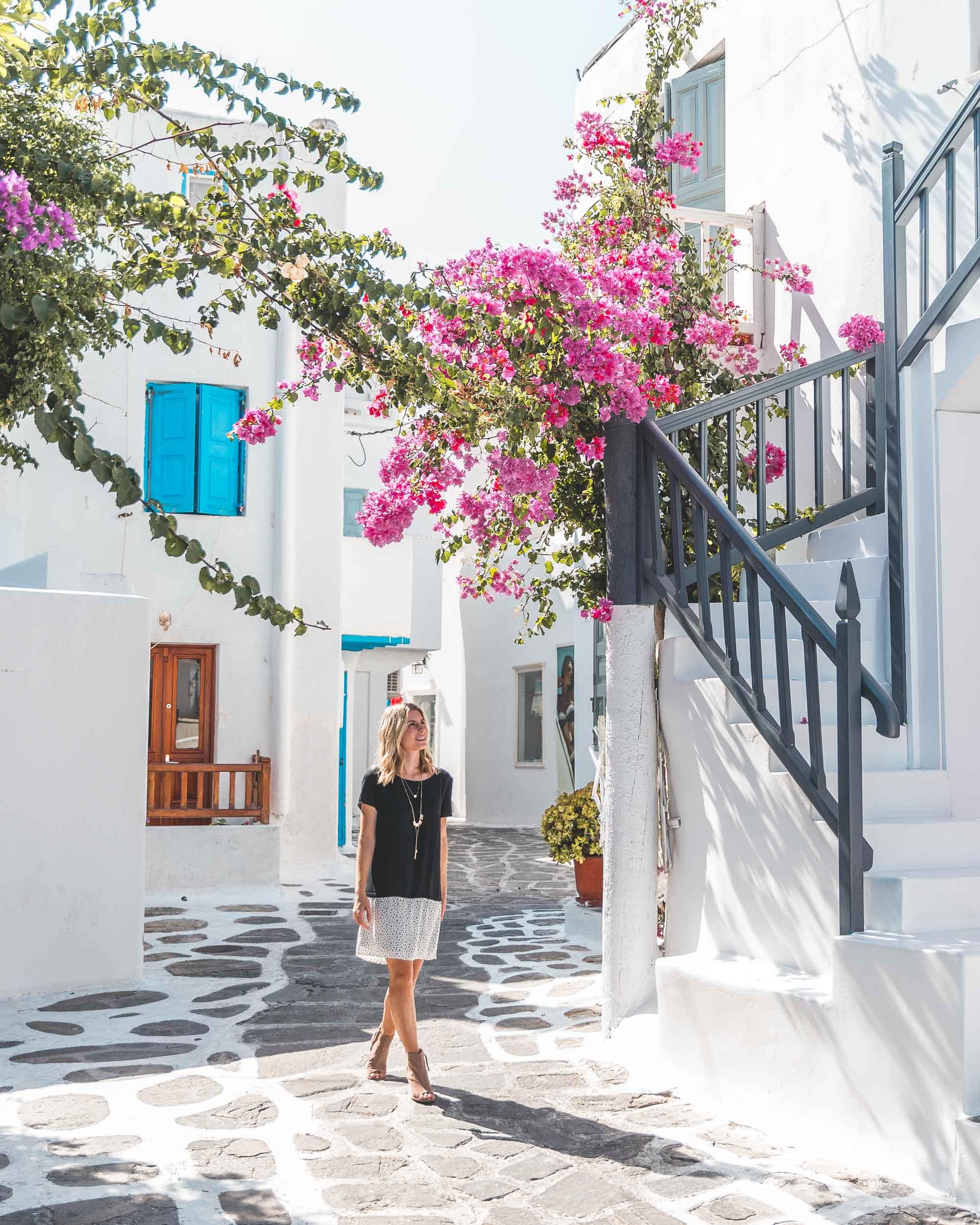 Downtown mykonos cobblestone streets and pink flowers white houses blue doors greek islands greece