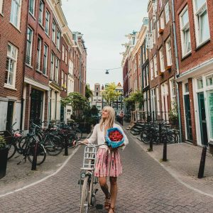 A girl with tulips and her bike on the canals in Amsterdam, The Netherlands