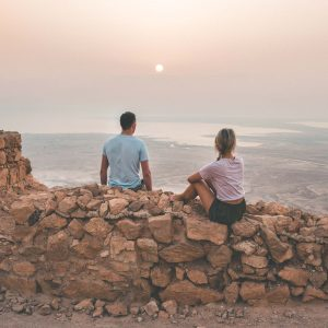 Couple watching sunrise over Masada hike in the dead sea in Israel