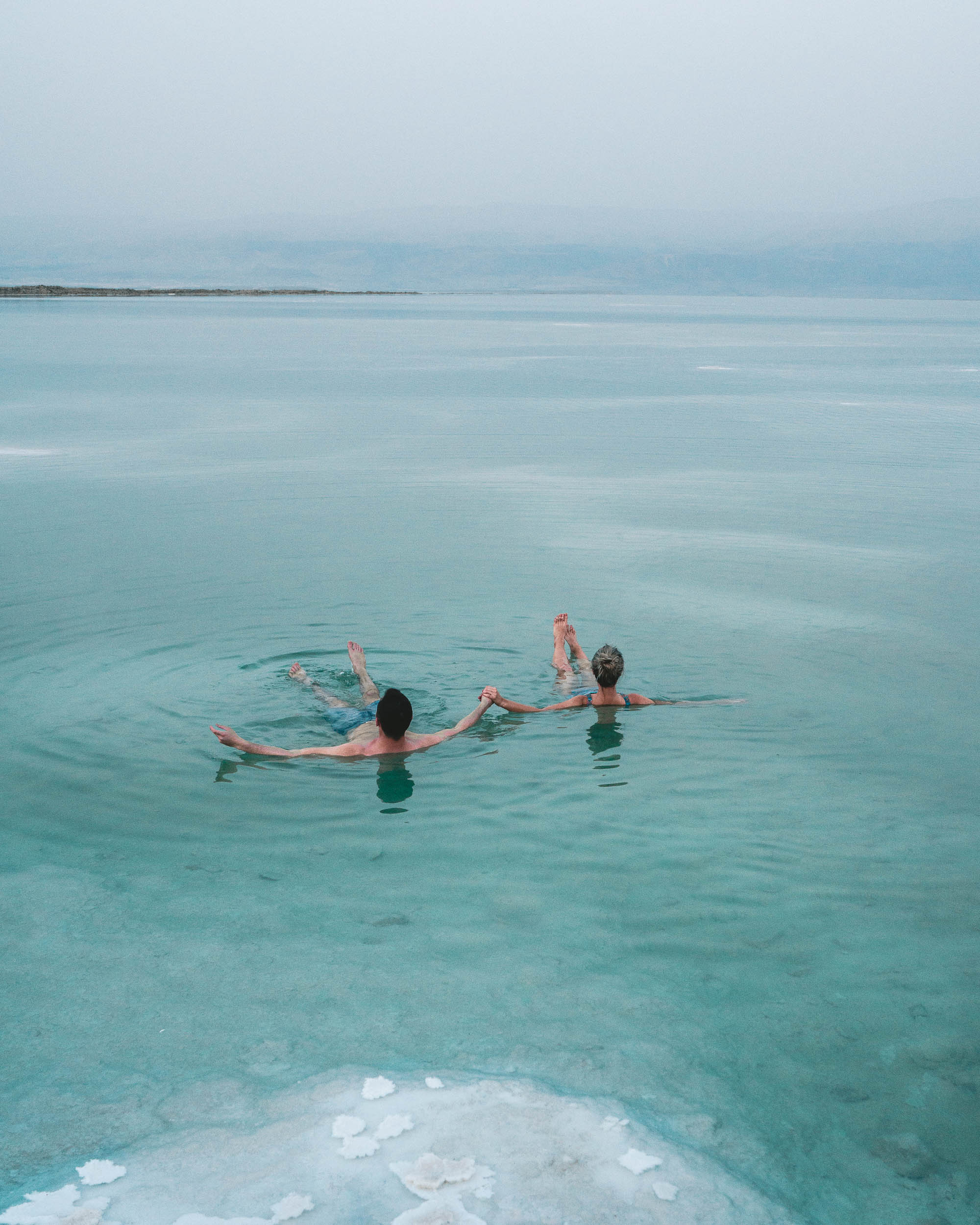 Couple floating in the dead sea together Israel Find Us Lost