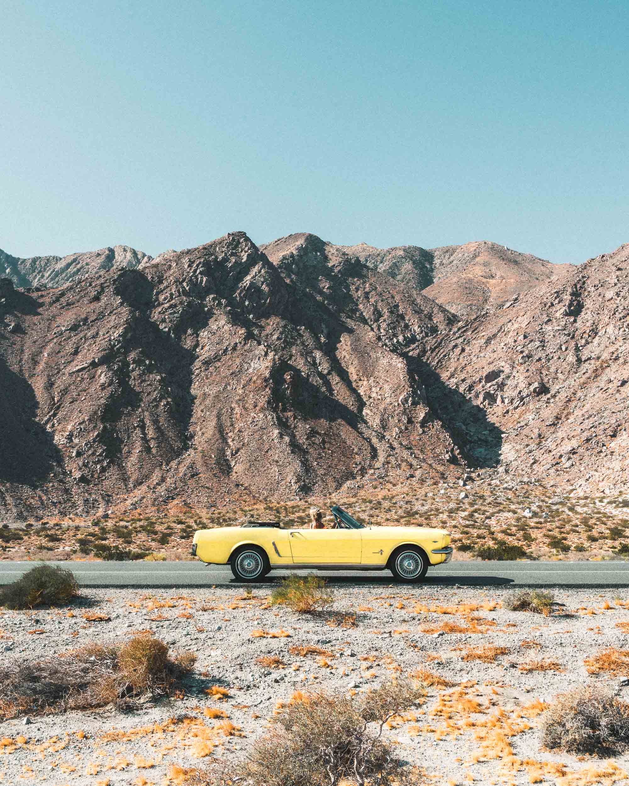 Vintage yellow car in the desert of Palm Springs California Find Us Lost