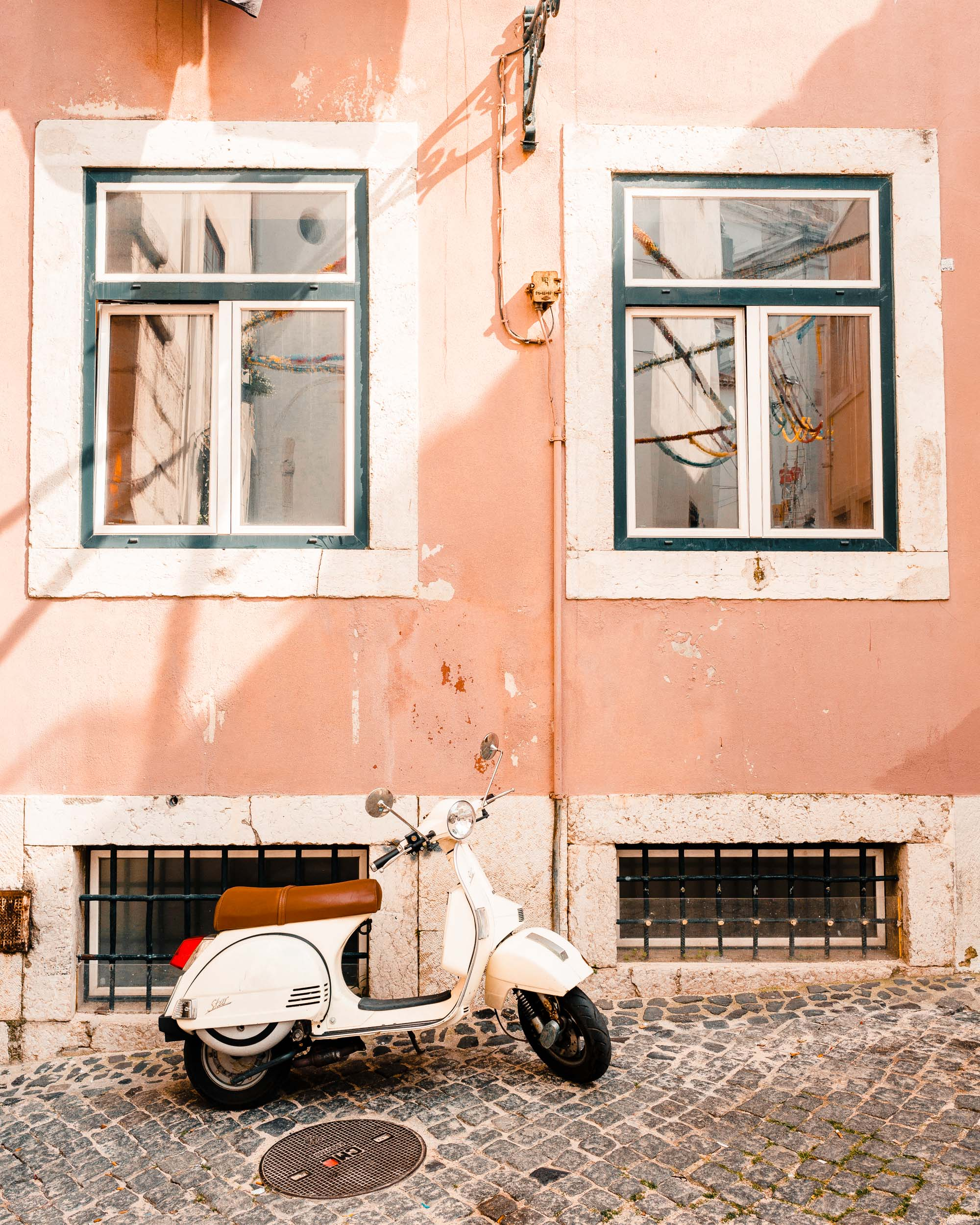 White motorcycle in front of a pink wall in Alfama, Lisbon, Portugal | Lisbon Travel Guide via Find Us Lost
