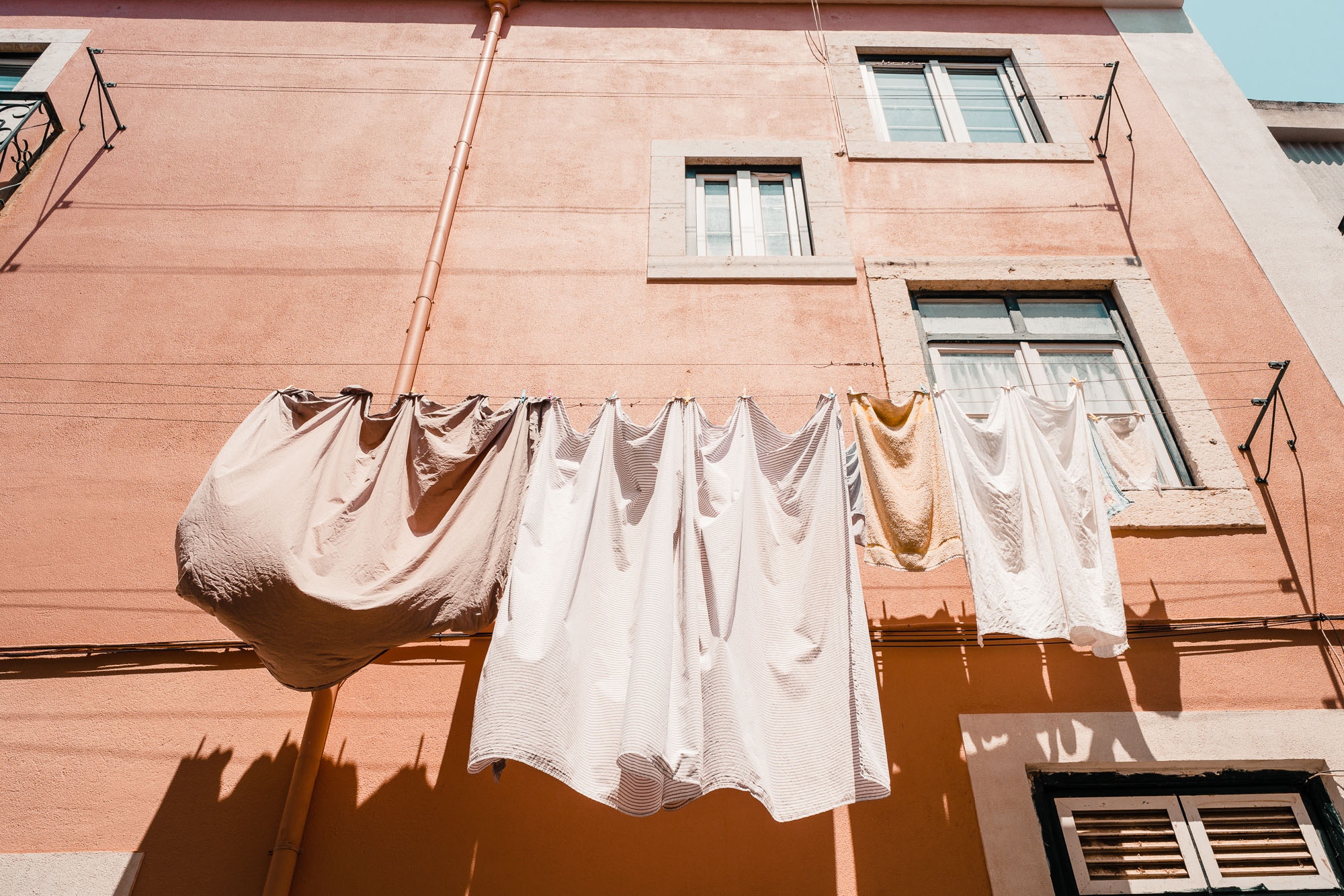 Hanging laundry on a pink building in Lisbon, Portugal | Lisbon Travel Guide via Find Us Lost
