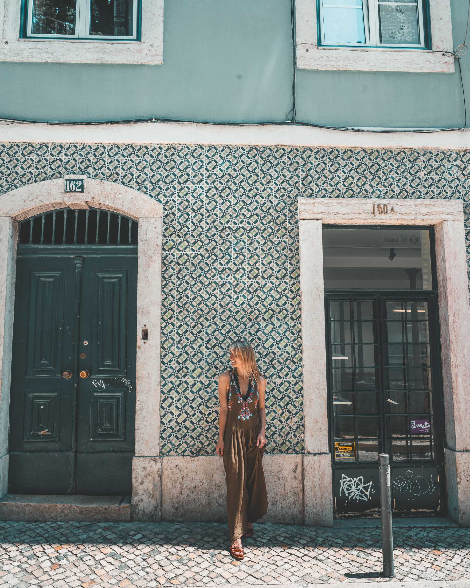 Taking photos in front of colorful tiled houses of Lisbon, Portugal | Find Us Lost
