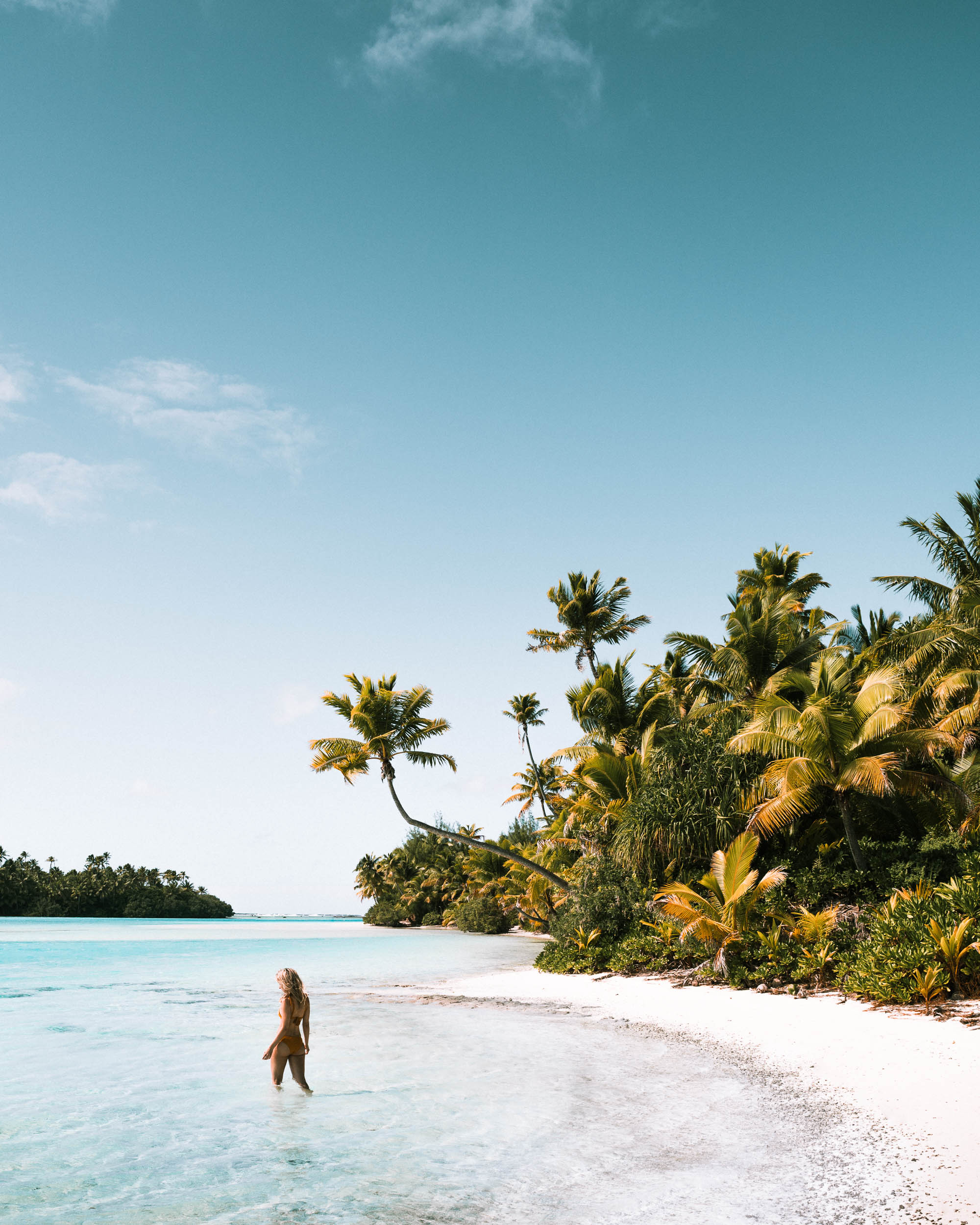 White sand beaches and palm trees and lying in the sand at One Foot Island in the Cook Islands