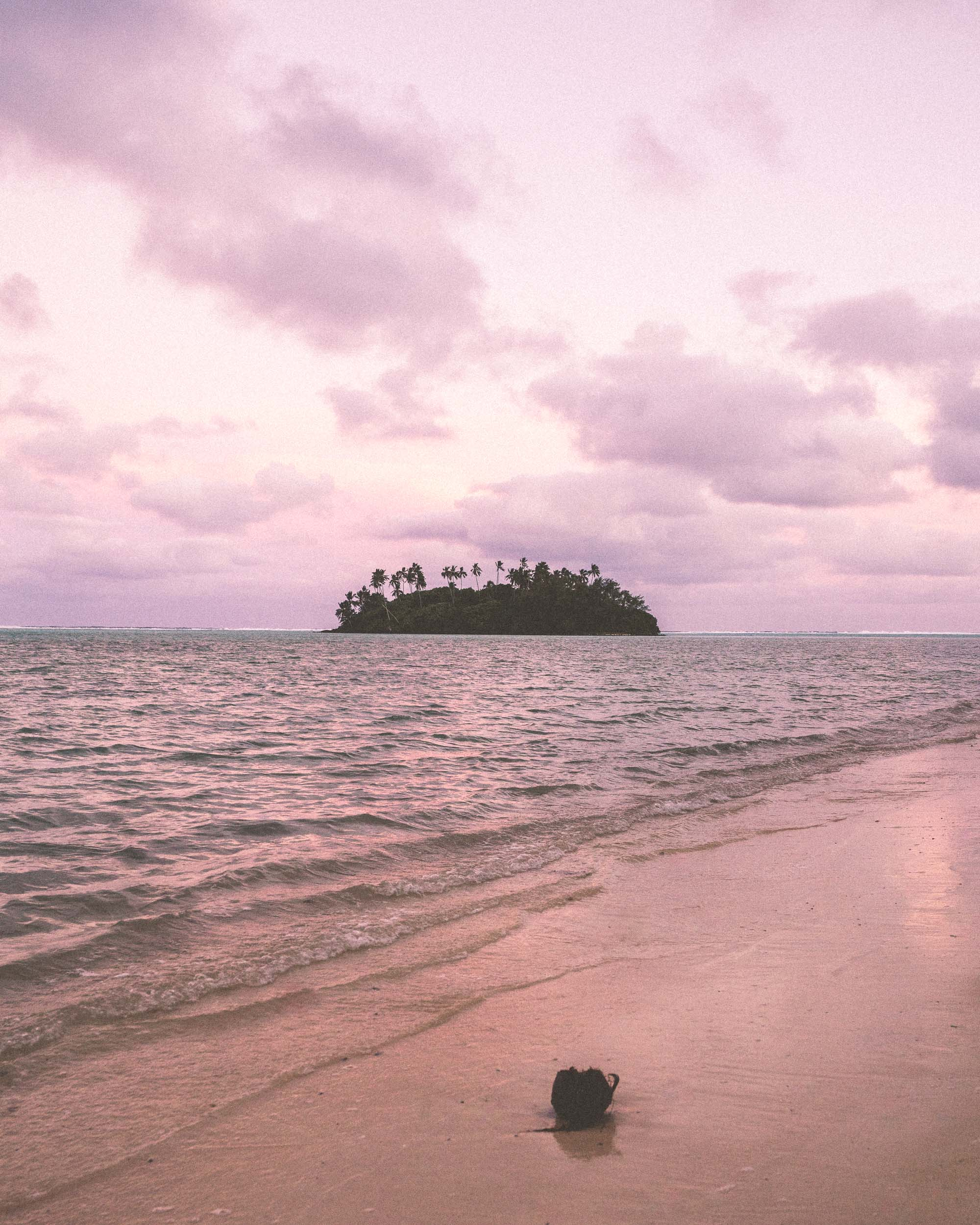 Sunset with a tropical island in the distance in Rarotonga, Cook Islands