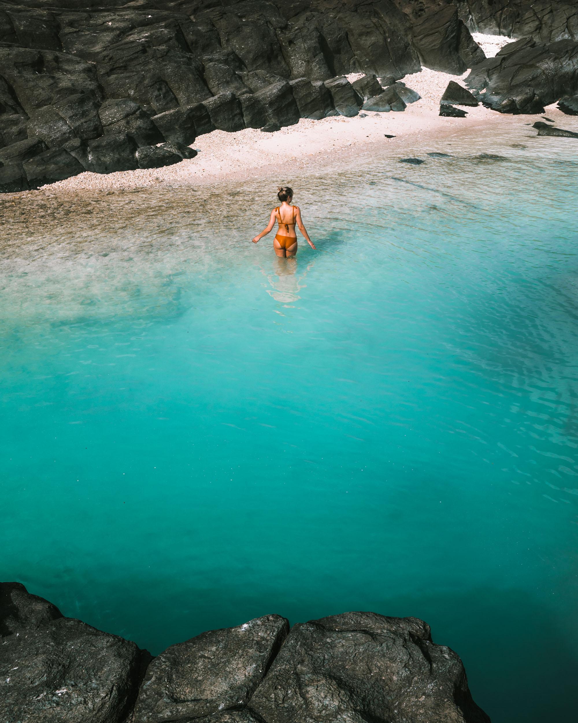 Swimming at black rock beach in Rarotonga, Cook Islands