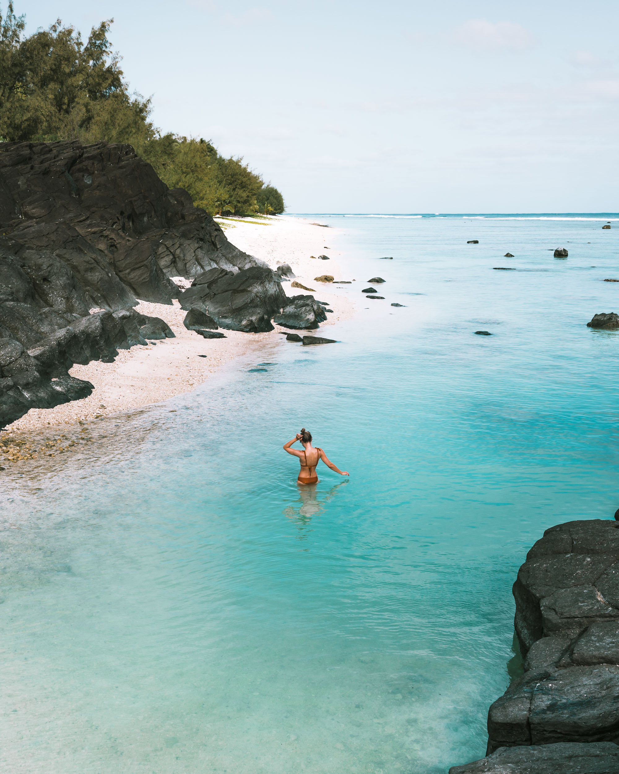 Swimming at black rock beach in Rarotonga, Cook Islands