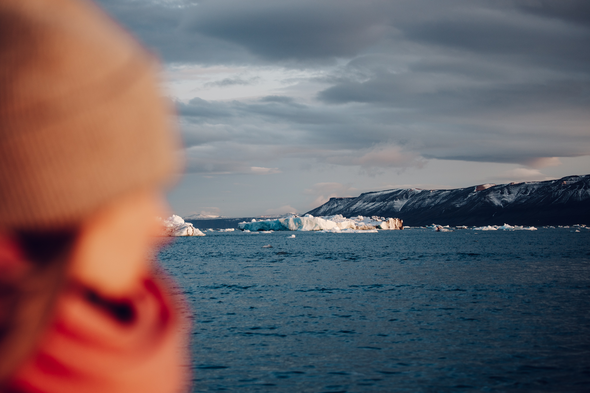 Ice floats from our zodiac in front of a glacier wall in Svalbard