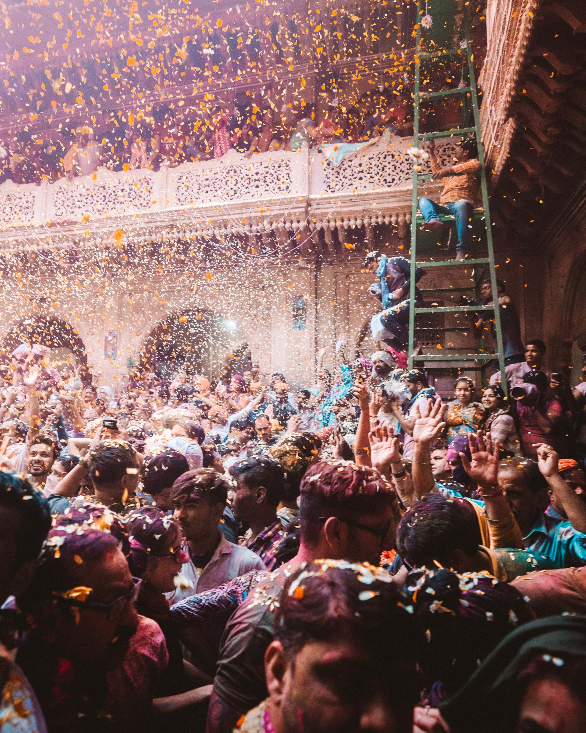 People celebrating with colorful powder and confetti during Pholoon Wali Holi Festival in Vrindavan, India via @finduslost