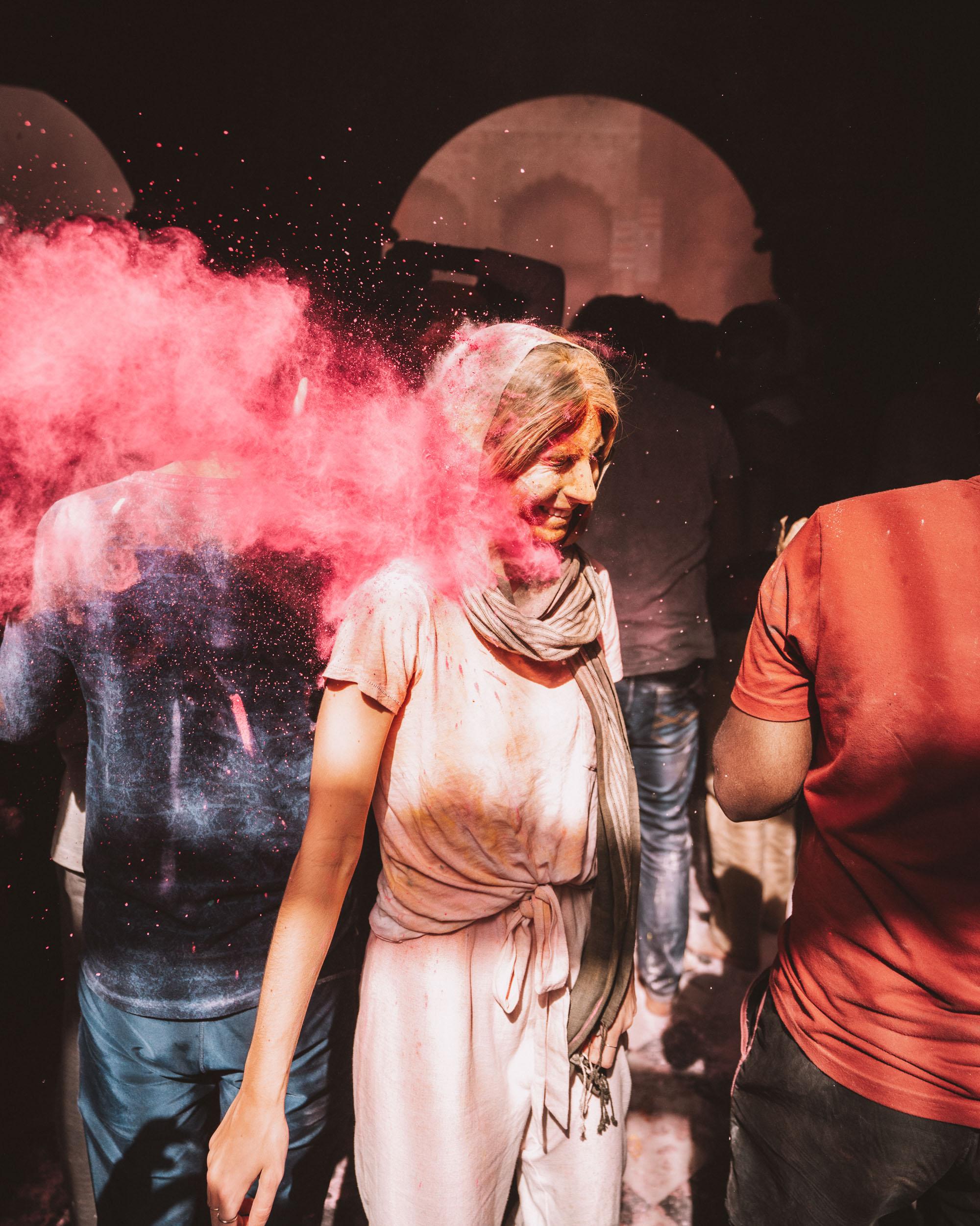 Pink powder being thrown at woman during Banke Bihari Holi Festival in Vrindavan, India via @finduslost