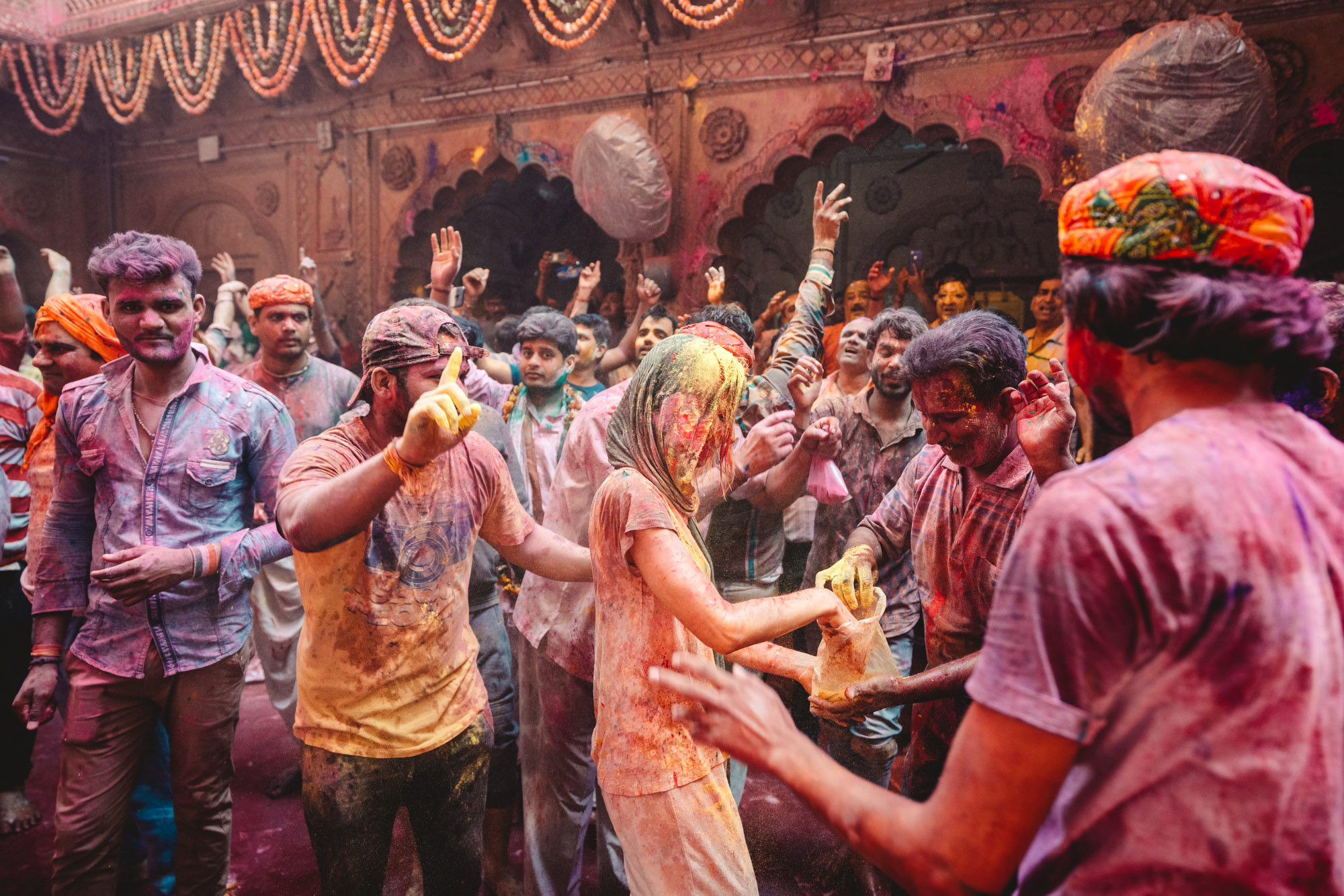 Woman and men covered in colorful powder, dancing during Holi Festival in Vrindavan and Mathura, India