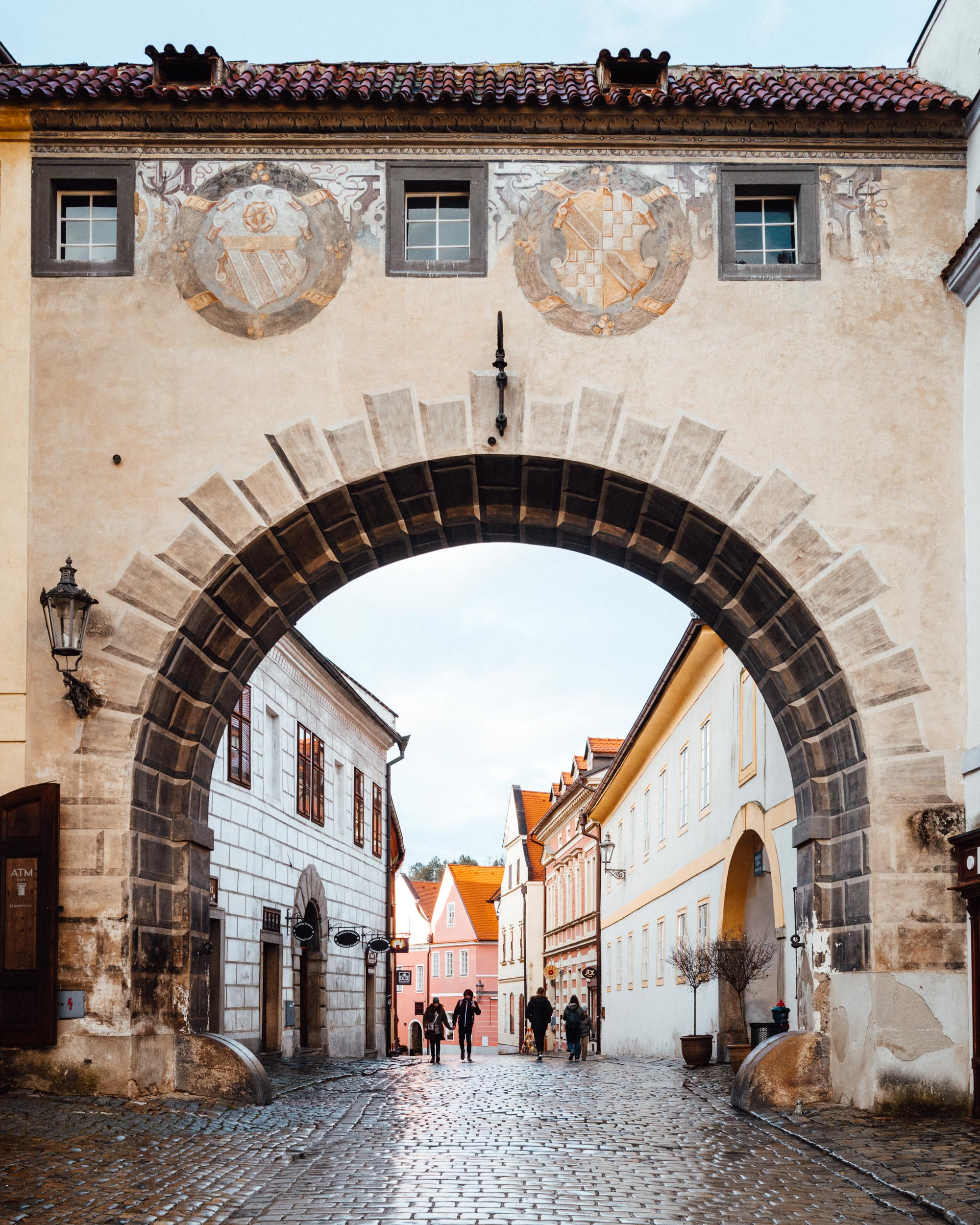 Medieval arch castle walls with people walking down the street of Cesky Krumlov Czech Republic